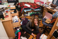 Picture of a very messy teenagers bedroom. A young teen girl is sitting on the floor of her unbelievably messy room.   Her drawers are open, clothes all over everywhere and piles of stuff all over the place. Untidy rooms.